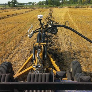 Farm equipment performing tile draining.