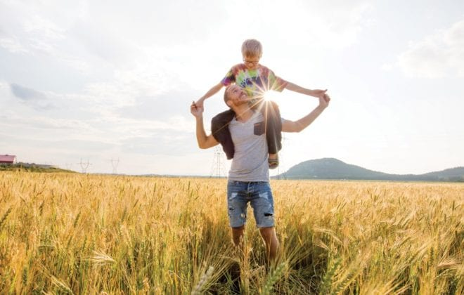 A young father with his little son walking in the wheat field at sunset in a warm summer day