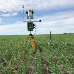 This almost-robot looking device is the John Deere Field Connects weather station that collects a wide range of environmental data such as rainfall, solar intensity and wind speed. The weather station also ties into the moisture probe which is installed near the steel post at right.