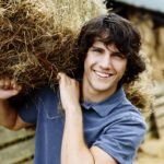 Young Farmer Carrying a Bale of Hay