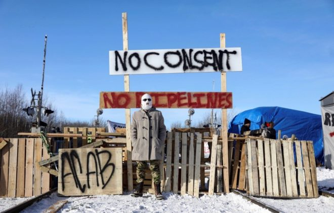 A demonstrator stands at a blockade on CN track west of Edmonton on Feb. 19, 2020. (Photo: Reuters/Codie McLachlan)