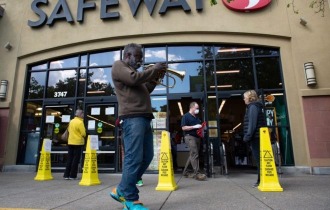 Reginald Conyers, a traveling busker, plays the trumpet outside a Safeway while people observing social distancing wait in line to enter the store  in Oakland on March 20, 2020. (Photo: Reuters/Kate Munsch)
