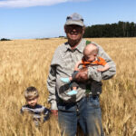 Grandpa John poses with Joseph and James in the barley crop