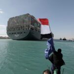 A man waves an Egyptian flag after the Ever Given, one of the world's largest container ships, is fully floated on the Suez Canal in Egypt on March 29, 2021. (Photo: Suez Canal Authority handout via Reuters)