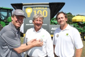 Jon Kennedy, left, president of Glacier Farm Media pins a 100-bushel canola button on  Rob Saik of Agri-Trend Agrology, as Glen Walsh of John Deere looks on.